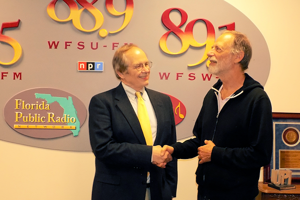 Tom Flanigan and Marty Klein shake hands in front of the radio station's graphics.